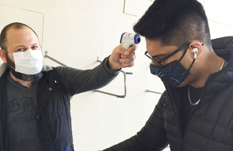 A student gets his temperature screened and recorded before entering the campus